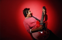 Young man with guitar, standing against red background - Asia Images Group