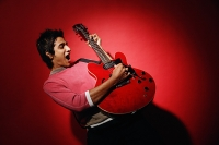 Young man playing guitar, standing against red wall - Asia Images Group
