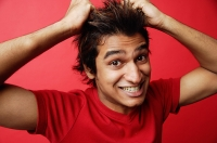 Man in red T-shirt against red background, pulling hair - Asia Images Group