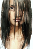 Young woman looking at camera, long wet hair covering her face - Asia Images Group