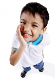 Young boy looking up at camera, hand on chin - Asia Images Group