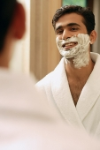 Man with shaving cream on face, looking in mirror - Asia Images Group