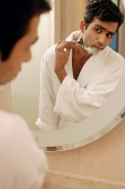 Man looking in bathroom mirror, shaving his face - Asia Images Group