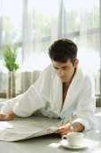 Man in bathrobe, lying on floor, reading newspaper - Asia Images Group