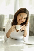 Woman smiling at camera, holding cup - Asia Images Group
