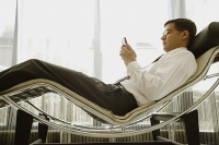 Businessman reclining on chair, using PDA - Asia Images Group