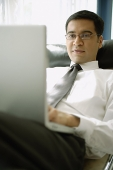 Businessman reclining on chair with laptop - Asia Images Group