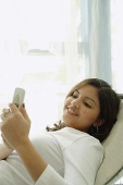 Woman lying on chair, looking at mobile phone - Asia Images Group