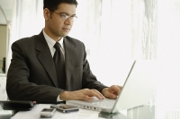 Businessman sitting at desk, using laptop - Asia Images Group