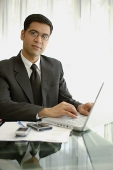 Businessman sitting at desk with laptop, PDA and mobile phone - Asia Images Group