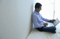 Man sitting on bed, using laptop - Asia Images Group