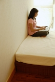 Woman at home, sitting on bed, using laptop - Asia Images Group