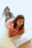 Woman at home, lying on bed, arms crossed, laptop open in front of her - Asia Images Group