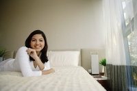 Woman lying on bed smiling at camera - Asia Images Group