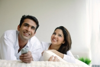 Couple lying on bed, watching TV - Asia Images Group