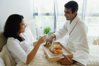 Couple in bedroom, man serving woman breakfast in bed - Asia Images Group