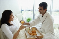 Couple in bedroom, having breakfast in bed - Asia Images Group