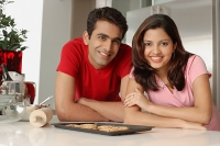 Couple leaning on kitchen counter, looking at camera - Asia Images Group