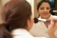 Woman applying blusher, looking in mirror - Asia Images Group