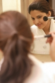 Woman applying blusher - Asia Images Group