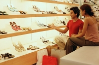 Man and woman in shoe shop - Asia Images Group