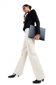 Business woman with mobile phone, carrying folder, low angle view - Asia Images Group