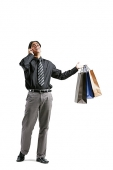 Businessman talking on mobile phone, carrying shopping bags - Asia Images Group