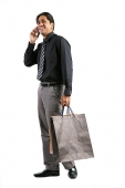 Businessman carrying shopping bags, talking on mobile phone - Asia Images Group