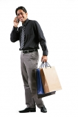 Businessman carrying shopping bags, talking on mobile phone, smiling at camera - Asia Images Group