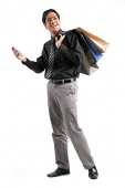 Businessman carrying shopping bags over shoulder, holding mobile phone - Asia Images Group