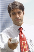 Businessman holding mobile phone towards camera - Asia Images Group