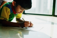 Boy lying on floor, drawing with crayons - Asia Images Group