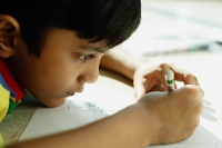 Boy with chin on floor, drawing with crayons - Asia Images Group