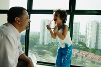Father and daughter looking at each other, daughter holding sunglasses, laughing - Asia Images Group