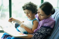 Daughter sitting on mothers lap, reading a book - Asia Images Group