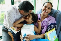 Family with one child, father kissing daughter's head, mother smiling at camera - Asia Images Group