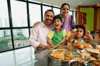 Family of four sitting around dining table, smiling at camera - Asia Images Group