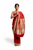 Woman in traditional Indian costume, standing with hands together - Asia Images Group