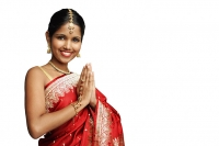 Woman in traditional Indian costume standing against white background, smiling at camera - Asia Images Group