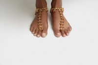 Woman's feet with anklet against white floor - Asia Images Group