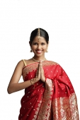 Woman in traditional Indian costume, standing with hands together, smiling at camera - Asia Images Group