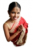 Woman in sari, standing with hands together, smiling up at camera - Asia Images Group