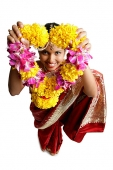 Woman in sari, holding flower garland up towards camera - Asia Images Group