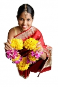 Woman in sari, holding flower garland, smiling - Asia Images Group