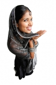 Woman in gray sari standing against white background, smiling up at camera - Asia Images Group