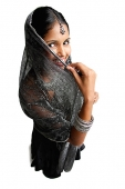 Woman in gray sari standing against white background, shielding face scarf - Asia Images Group