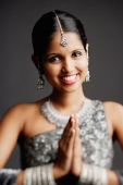 Woman in gray sari smiling at camera, hands together - Asia Images Group