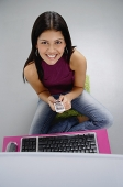 Woman sitting in front of laptop, holding mobile phone, smiling at camera - Asia Images Group
