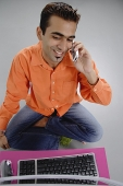 Man sitting in front of laptop, using mobile phone - Asia Images Group