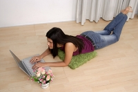 Woman lying on floor, using laptop, high angle view - Asia Images Group